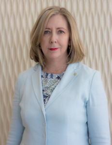 Picture of Helen Watchirs, Human Rights and Discrimination Commissioner wearing a blue jacket against a cream coloured walll